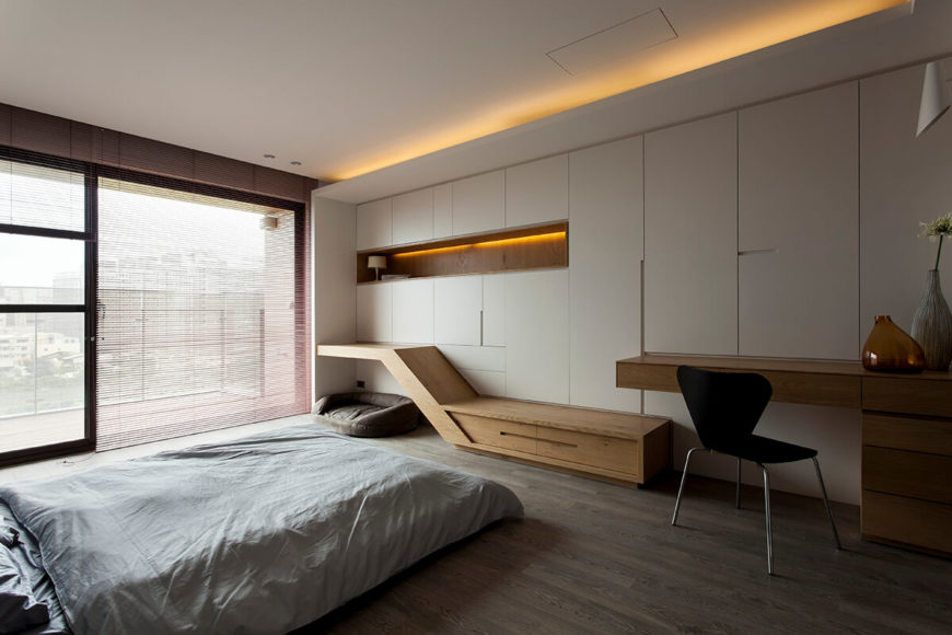 The bedroom is naturally lit via more of the full height windows, at left, and features direct access to the balcony. Both a minimalist desk and sloped storage/end table combination are built into the white paneled wall.