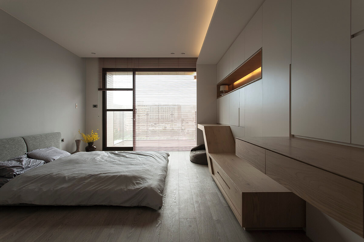 The contemporary master bedroom features a gray floor bed facing the built-in wooden shelves and storage cabinets.