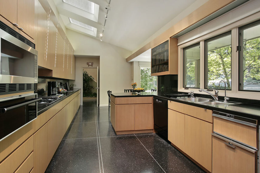 In a lengthy and deeply contemporary kitchen, speckled black flooring and glossy black countertops contrast with the white walls and open, sunlit space. Natural wood cabinetry surrounds the area, sunlit through abundant windows and skylights. A discreet bookshelf is built into the right wall, with smoked glass cabinet doors.