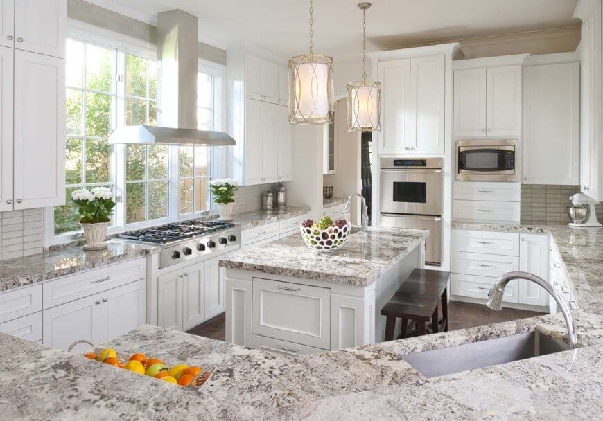 In a kitchen flush with elegant style, granite countertops adorn nearly every horizontal surface. The large island is complemented by surrounding white cabinetry and a lengthy wraparound countertop. Above the large stainless steel range, an immense set of windows fills the entire kitchen with sunlight.