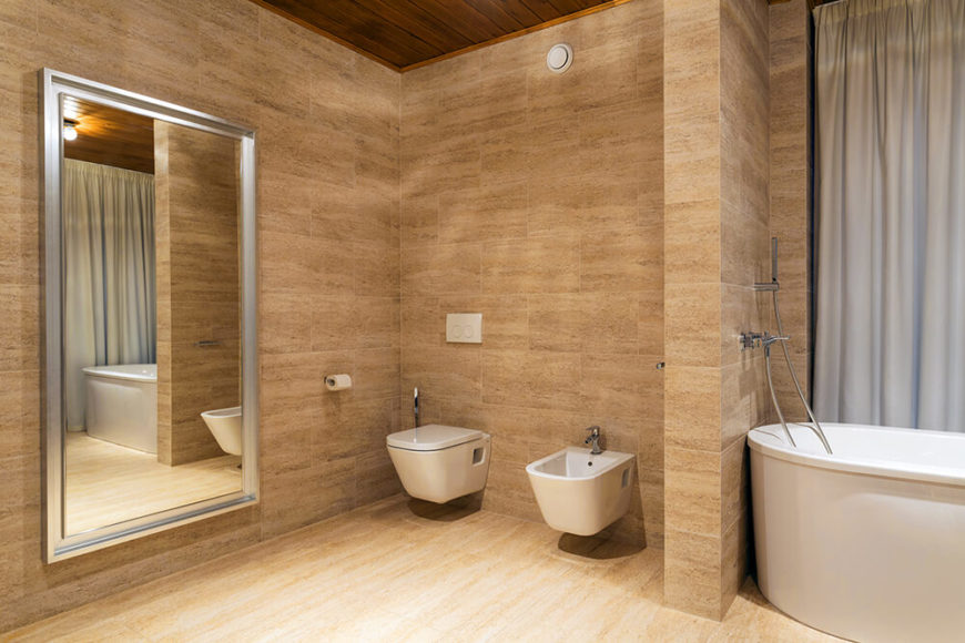 The master bathroom is fully tiled in a rich, warm beige, and features a small privacy wall separating the soaking tub from the commode. A full-length bathroom mirror is visible to the left.
