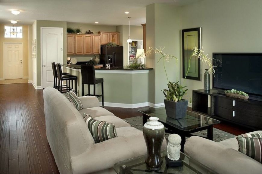 This much more casual main living area features a light sage green wall color in both rooms, which helps them flow together. Visitors enter the space immediately upon entering the home, which is typical of Ranch style homes.