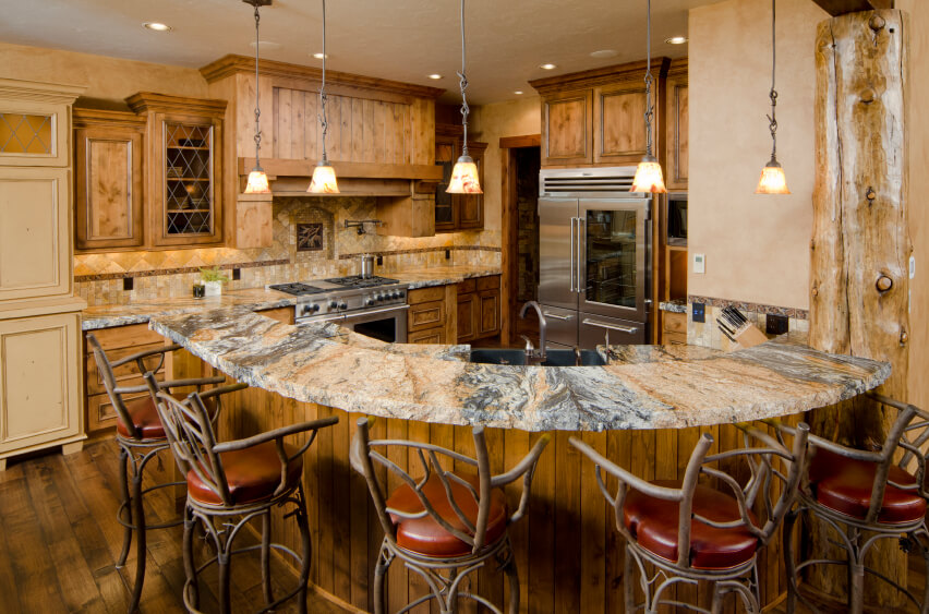 This richly appointed and luxuriously rustic kitchen wraps its natural wood cabinetry with bold marble countertops and nearly matching tile backsplash. The curved and raised tier in the foreground offers ample space for numerous in-kitchen diners. In a splash of inspired joy, the bar stools are framed with tree branch-look metal, aiding the homespun atmosphere.