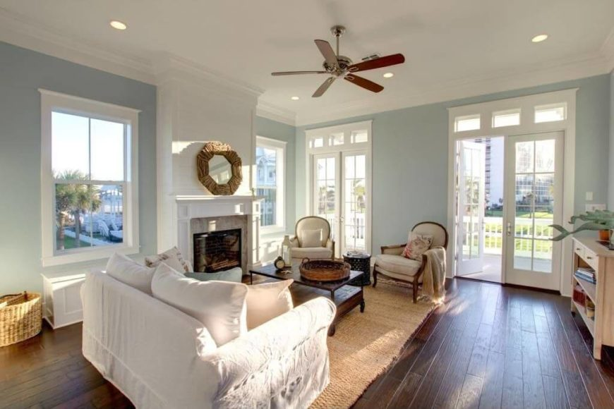 This room's pale palette is warmed up by the inclusion of red wood tones in the furniture, ceiling fan, and floor. all of this stands out well against the powder blue and bright white.