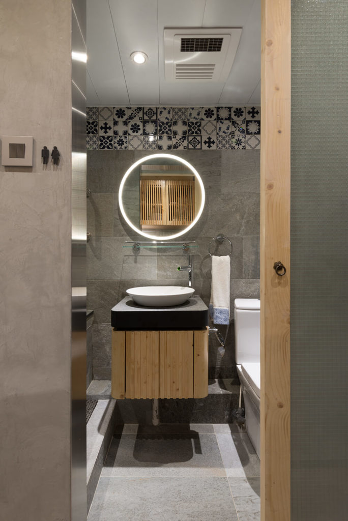 The bathroom is overflowing with unique modern luxury touches, from the floating vanity with vessel sink to the intricate tile work on the upper wall. An illuminated mirror makes for a bold impression and high utility.