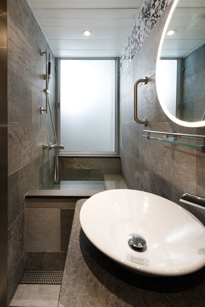 The bathroom is defined by its grey stone cladding, entirely distinct from the remainder of the home. Smoked glass here allows in natural light while granting privacy.