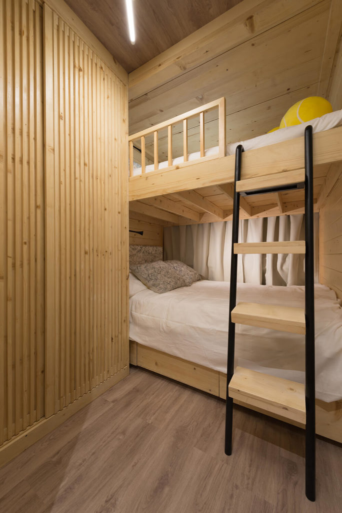 The upper bunk can be converted for storage, or both can be used to sleep extra people. A slim ladder framed in black adds a splash of contrast to the natural wood room.
