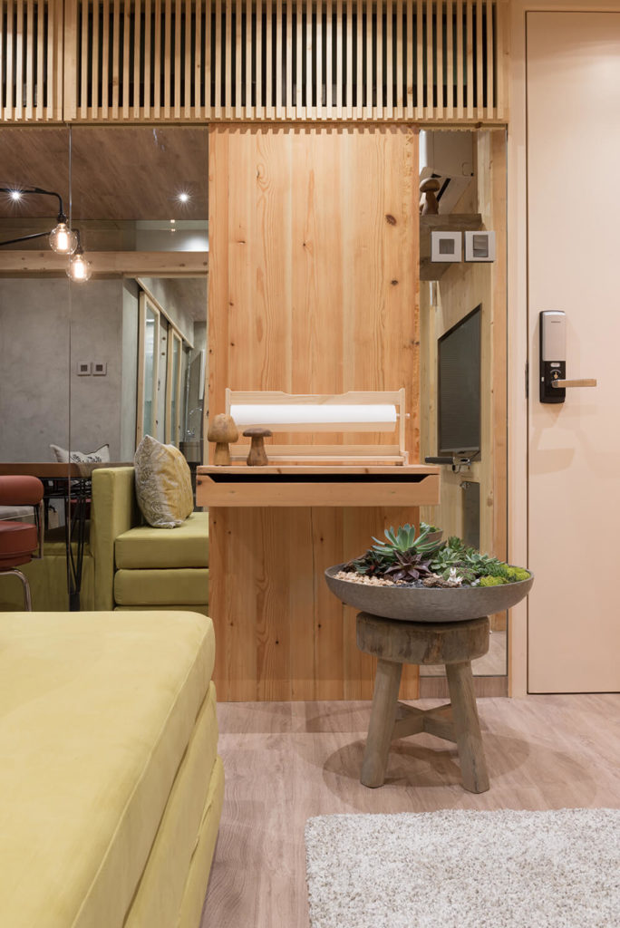 As virtually everything within this home can be converted, transformed, and reconfigured, we see the built-in desk standing above a rustic wood stool that now holds a wide succulent garden container.