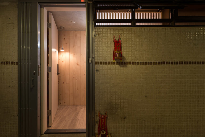 The exterior entryway showcases the vast improvements made within the home. The contrast between dank tile walls and the bright natural wood interior could not be more stark.