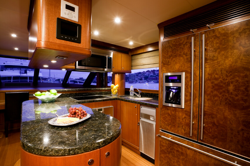 Even on a boat, you can enjoy the luxury of a G-shaped kitchen. This design necessarily packs a lot into a small space, with dark granite countertops and rich wood cabinetry boasting a carefully considered sense of contrast. With everything fit so tightly together, it's amazing to see the variety of appliances and useful countertop space.