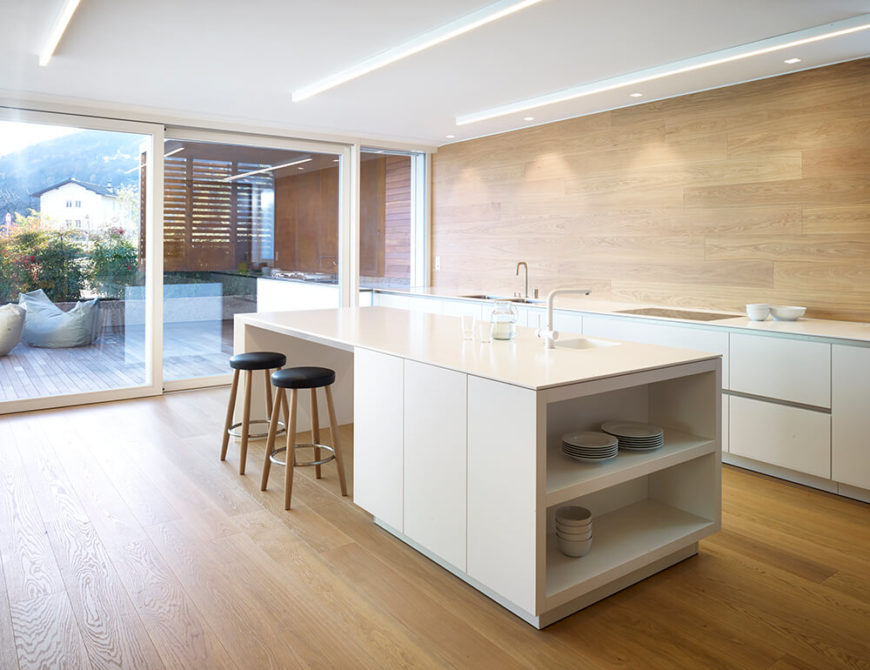 A full view of the kitchen shows simple minimalist white lower cabinets, with no wall cabinets. To the left we can see the patio and wooden pergola. The kitchen island also has room for two at a breakfast bar.