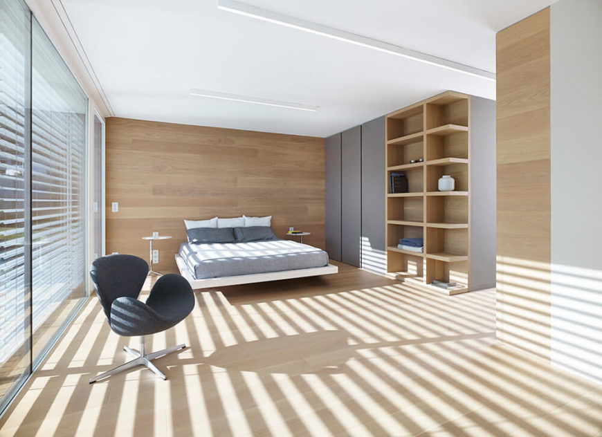 The master bedroom is as spacious as the other rooms in the home sand features bookshelves and minimalist storage in gray. Darker wood on the wall behind the bed serves as a subtle accent.