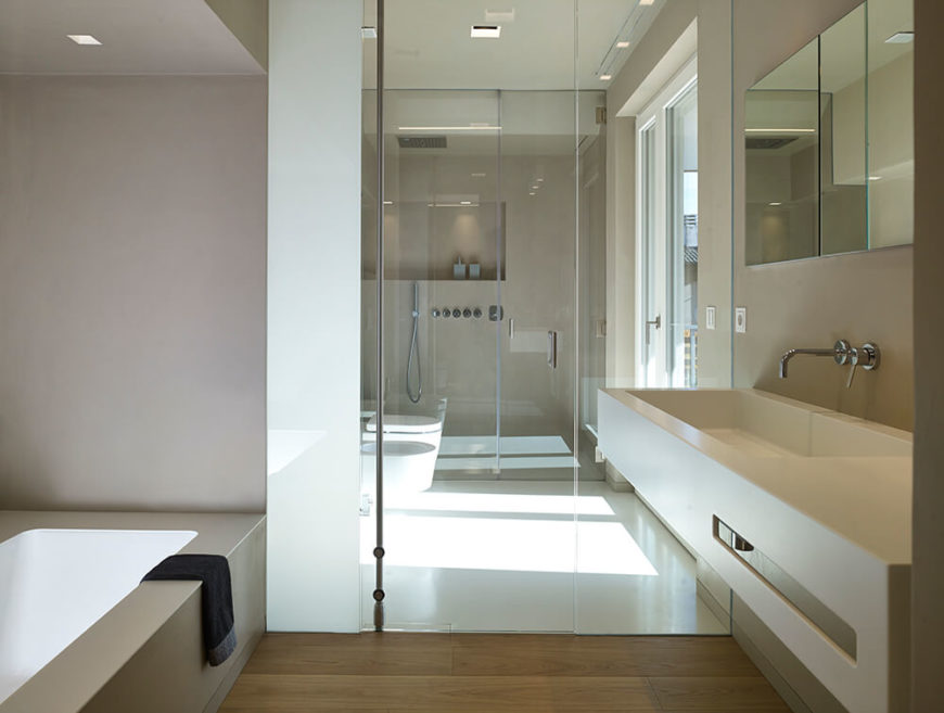 The master bathroom features a similar design to the downstairs bathroom, with the inclusion of a large soaking tub. The shower and commode are tucked into separate wetrooms, with a door leading out to a terrace.