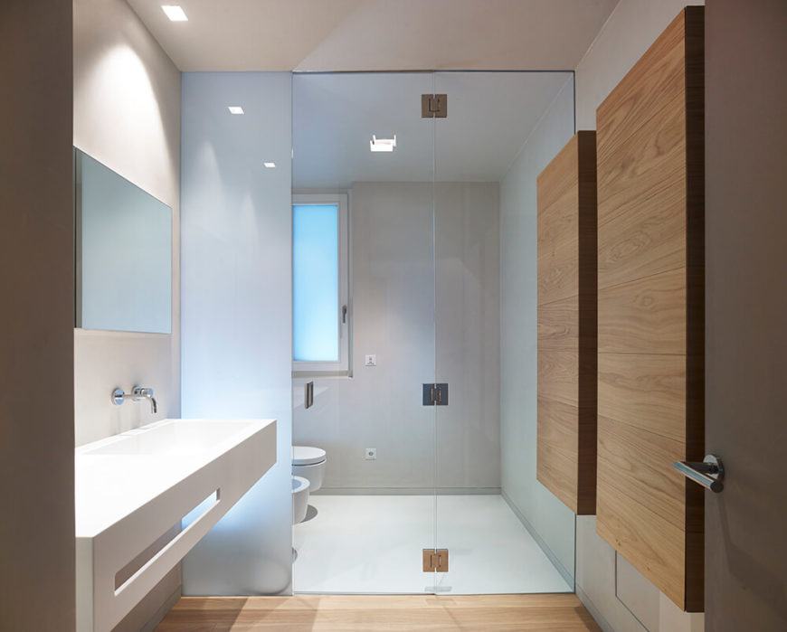 The ground floor bathroom features a wet room that contains the commode behind a privacy screen. The sink consists of one long trough and two wall-mounted faucets.