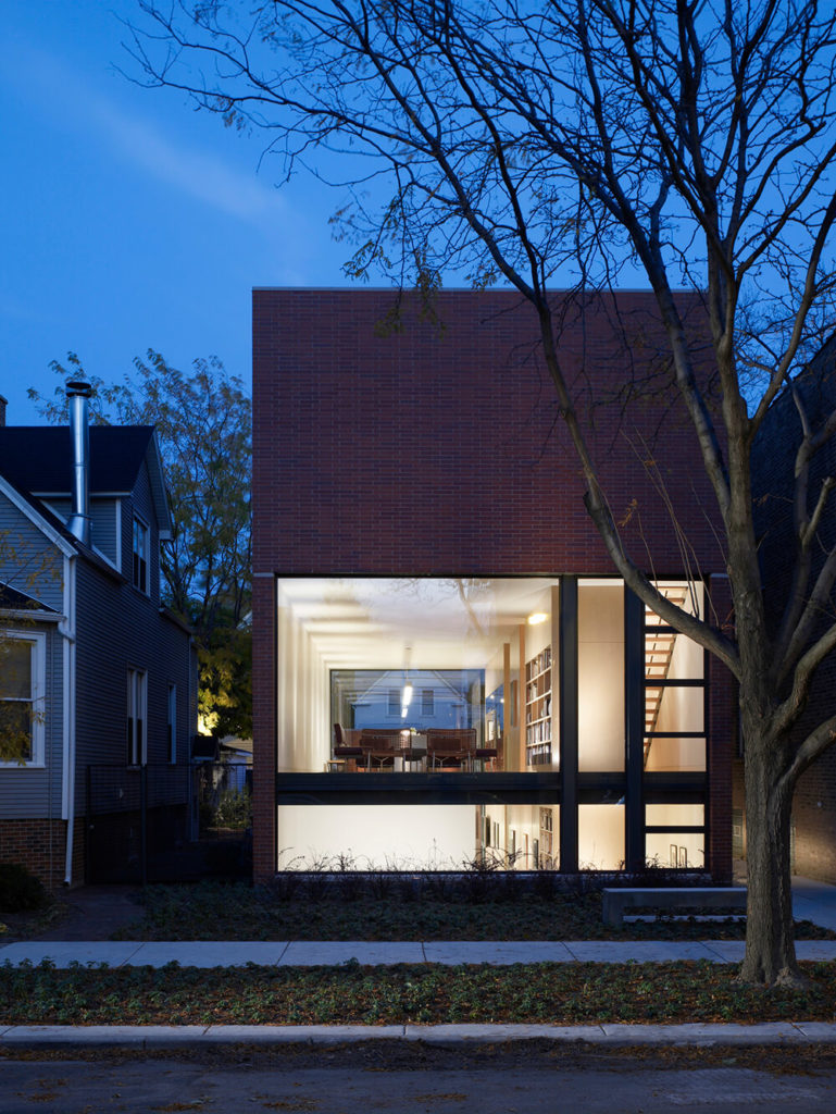 Here's the full front view of the home, at street level. The minimalist cube shape is wrapped in traditional red brick, but barely conceals its innovative nature, glowing outward through massive windows.
