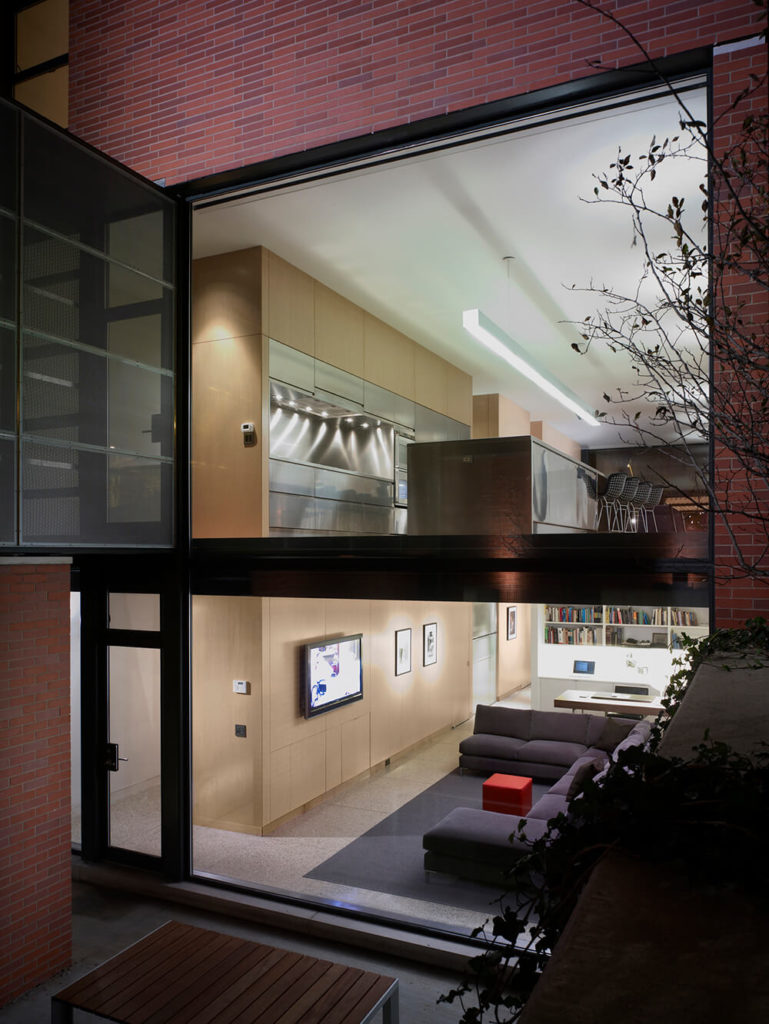 A close look from the rear courtyard of the home reveals the first and lower floors in startling detail. From here we can see both the family room and the kitchen, highlighted by the massive stainless steel island.