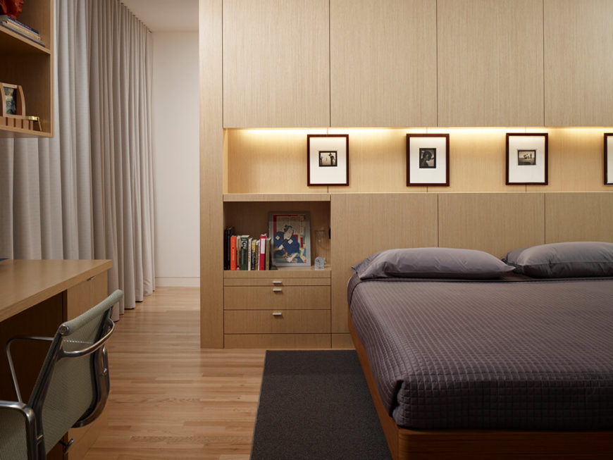 The primary bedroom sees more of the intricate but minimalist wood panel wall construction, giving way to a lighted display shelf and subtly disguised storage. Large curtains add privacy, a necessity with such tall windows.
