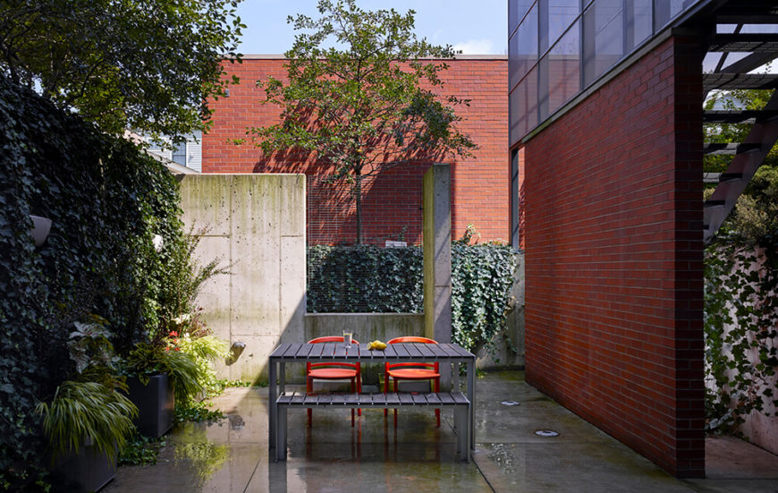 Here in the courtyard, loads of ivy and other greenery help obscure the sharply modern look of concrete walls. A single picnic table stands in this private oasis, perfect for outdoor family dining.