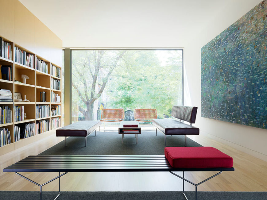 The massive open volume ends at a full size window, absolutely blurring the line between interior and exterior spaces as the nearby foliage fills the frame of view. More contemporary seating options join the minimalist space, next to a wall-size built-in bookshelf.
