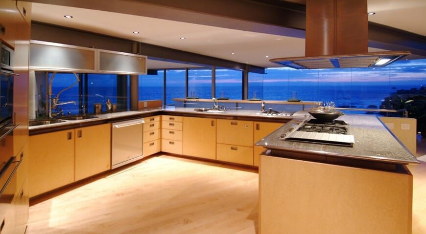This expansive, open plan kitchen enjoys broad views of the surrounding ocean via wraparound glazing, while steel-edged granite countertops stand in contrast to light wood cabinetry. The G-shaped configuration allows for a grand open space at center, allowing multiple cooks to share the kitchen. Stainless steel appliances and upper-level cupboards boost the modern appeal.