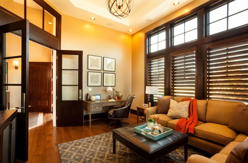 Here's an enormous home office, filled with rich furniture, including a light tan L-shaped sectional and button tufted leather ottoman. A set of large wood framed windows pour natural light into the space, entered via a set of glass panel French doors.