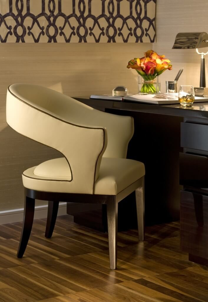 Richly textured hardwood flooring underpins this elegant home office, neatly complementing the textural beige walls. A cream toned leather upholstered chair stands next to a dark stained natural wood desk at center.
