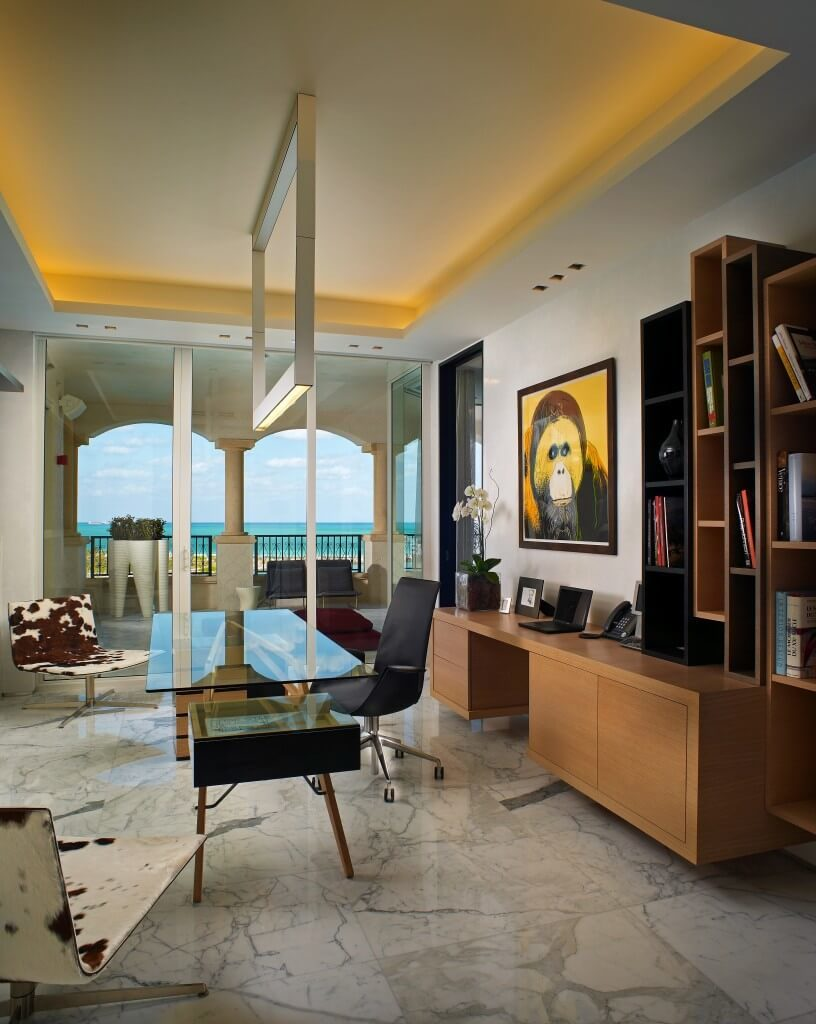 In a stately open plan space flush with marble flooring and white walls, we see a home office centered on a modern glass-top desk. Sunlight pours in via wraparound glazing, while a set of natural wood shelving and side desk fills out the space.