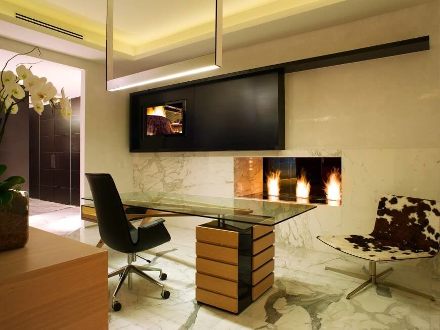 Here's the same home office from a new angle, showcasing the large gas fireplace cutout built into the marble wrapped wall. A singular open square frame holds the lighting directly above the desk.