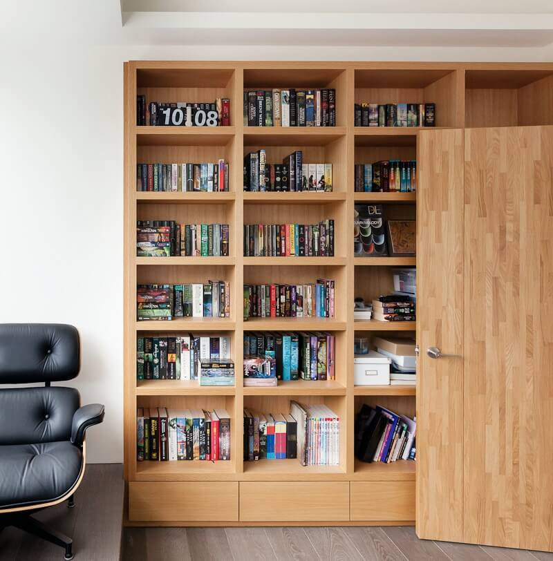 This home office takes advantage of the home's ultra-modern, minimalist design ethos, utilizing more of the varying shades of natural wood found throughout the interior. A large bookcase is built into the wall, contrasting with grey stained hardwood flooring.