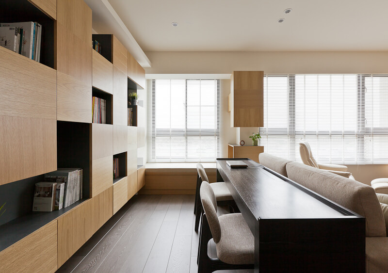 Within another home by the same designers, we see a similar set of varying shades of natural wood, arrayed in minimalistic fashion. The home office here is defined by a lengthy dark wood desk within a larger open living room space.