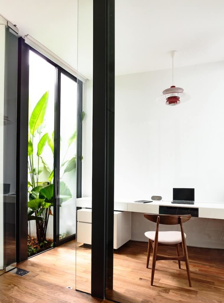 Here's another sleekly modern home with an office set into a larger open space. A set of sliding glass panels defines the room, while a glossy white desk with storage is built into the wall, over rich hardwood flooring.