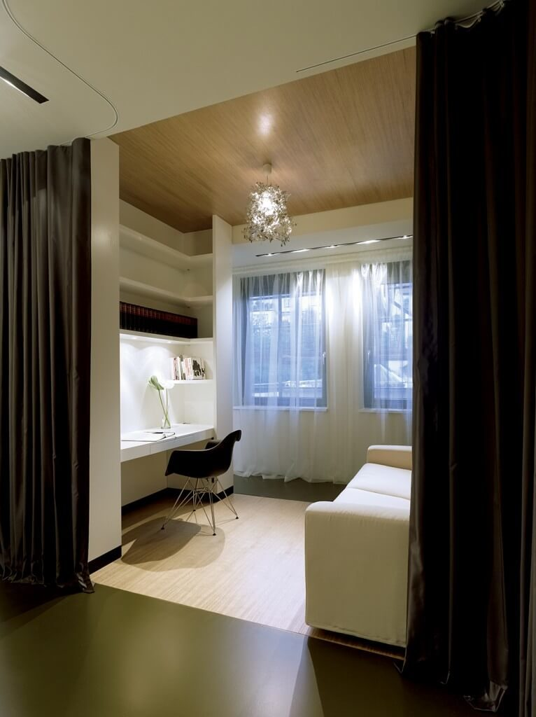In a large bedroom en suite, this home office stands behind a dividing wall that doubles as the desk itself. A strip of bamboo flooring at center defines the area, contrasting with dark flooring throughout.