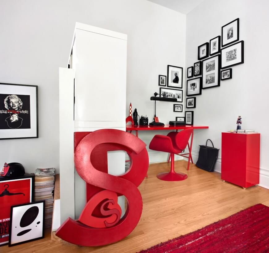 This large home office pairs white walls with rich hardwood flooring for a bright, classic look. Red furniture, rugs, and other artistic details punctuate the contrast with flair and life.