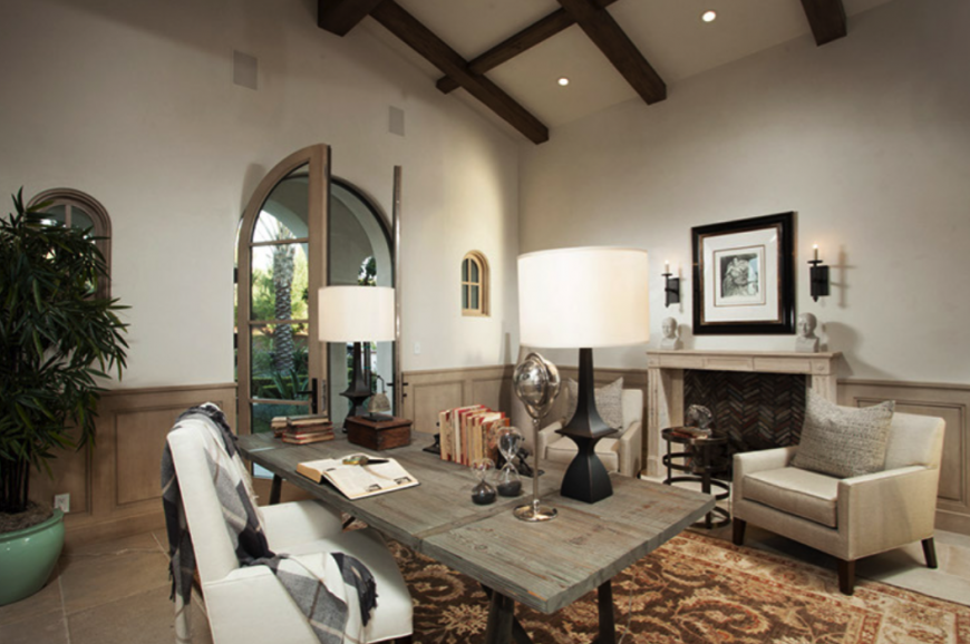 Beneath a massive vaulted ceiling with exposed wood beams, this large home office centers on a rustic wood desk and thick padded white leather office chair. A set of angular club chairs flank a fireplace at right.