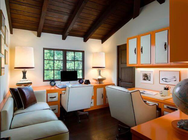 Rustic appeal and modern sleekness combine in this home office, with exposed natural wood beam ceiling and dark wood flooring hugging a bright space filled with color. Orange and white cabinetry and desk design offers a brilliant counterpoint to the rustic home design.