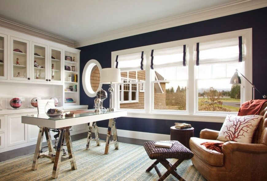 The bold combination of blue and white defines this large home office, with dark hardwood flooring obscured by a large area rug in white and baby blue. The desk features a glass surface over white slab construction, with chromed A-frame legs.