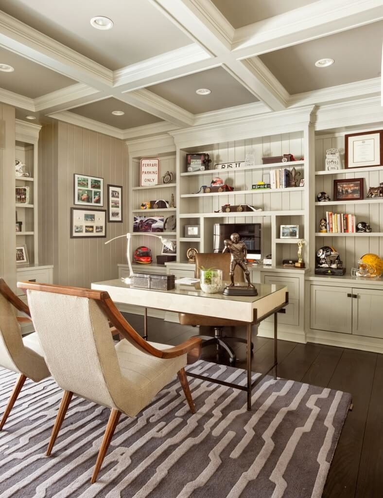 This massive home office features the bright contrast between dark stained hardwood flooring and white walls and rich cabinetry and shelving above. Beneath a detailed ceiling with recessed lighting, the desk appears as a white slab over thin metal frame.