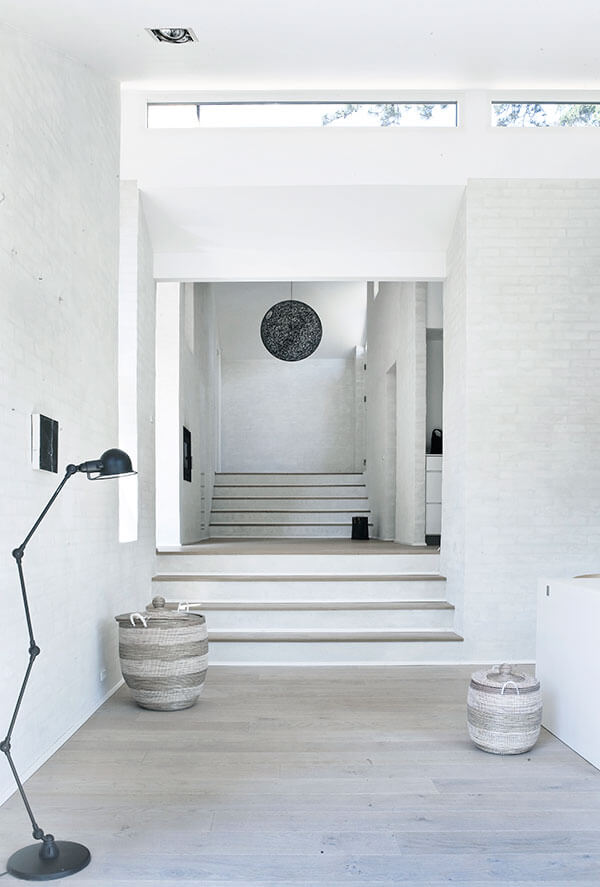 This white foyer is anything but simple. Filled with subtle shades and textures; the brick walls, weathered wood floors, and thickly woven baskets each add their own touch. Small black accents, such as the standing floor lamp and hanging pendant light, break up the use of white and pull the eye deeper into the house.