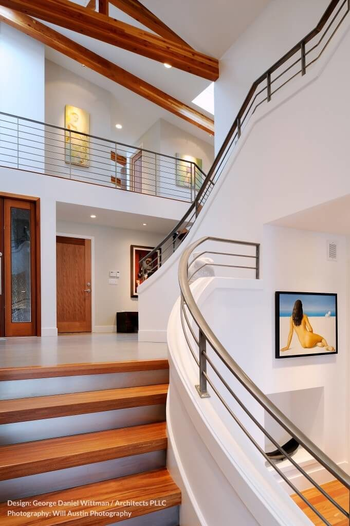 With multiple levels of sweeping staircases and soaring ceilings, this foyer is a great example of making a grand entrance. Pale concrete floors complement the white walls and the sleek metal railings lining the bright wooden stairs.