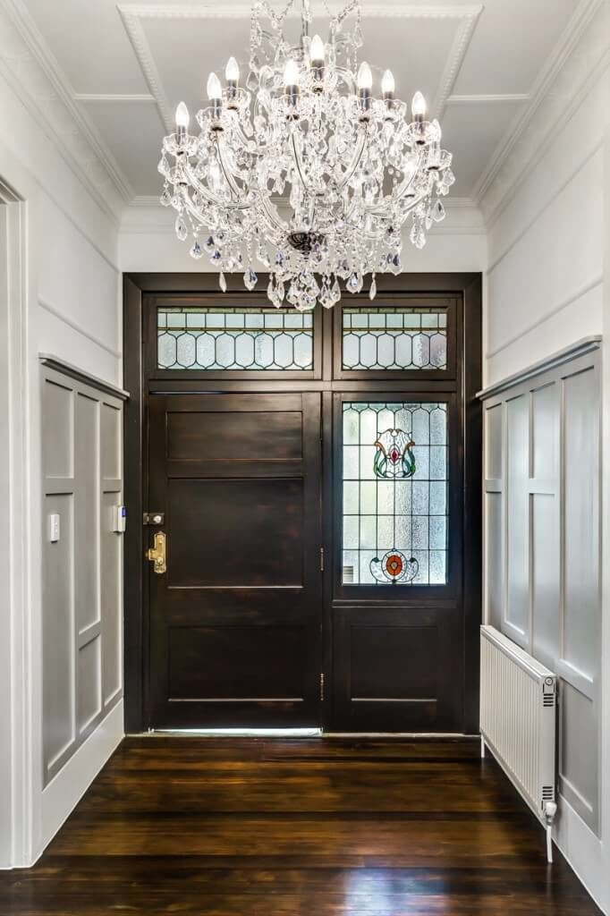 pale paneled walls and a stunning crystal chandelier balance the dappled tones of the beautiful wood foyer traditional entry - Foyer Tile Design Ideas