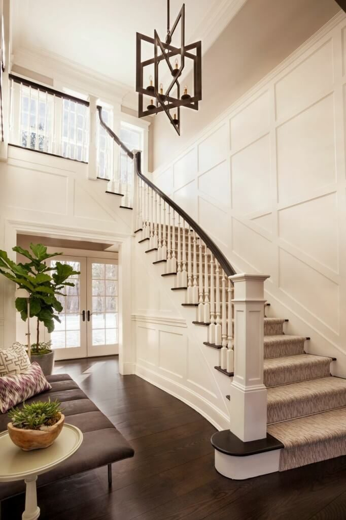 This soaring foyer houses a gorgeous geometric chandelier and a lovely staircase leaving the second