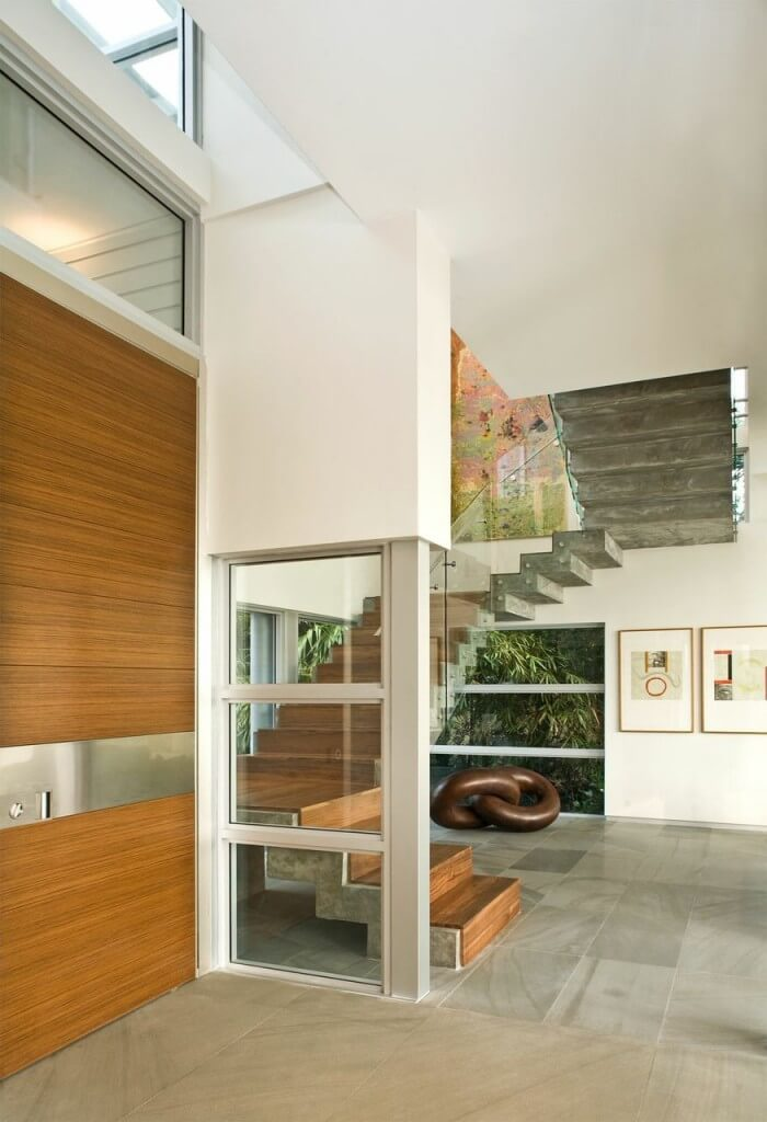 This breezy entrance features a floating stairway to make a striking statement. All the glass and open space is warmed by the exotic wood used in the door to the left and again in the stairs.