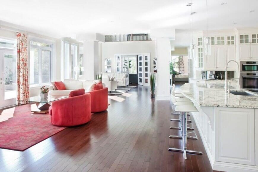 Bold reds in the living room area help distinguish it from the luxurious white marble kitchen visually, while still allowing the light pouring in through the glass doors and expansive windows to reach the kitchen area.
