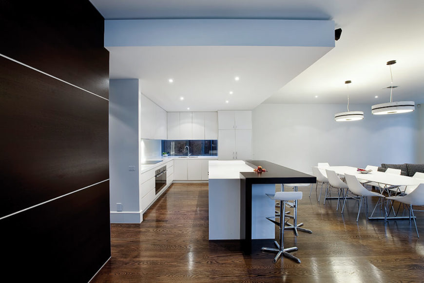 The center of the interior is a large open-plan space that combines the living room, dining, and kitchen functions over an expansive dark hardwood floor. The kitchen is seen here, defined by its massive island in black and white.