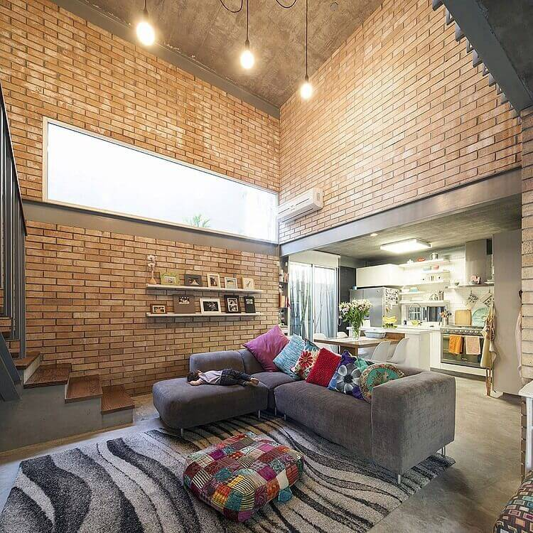 This all-brick living room flows into a dining room and kitchen with a much lower ceiling. Colors and patterns add a quirky atmosphere to this loft-style home.