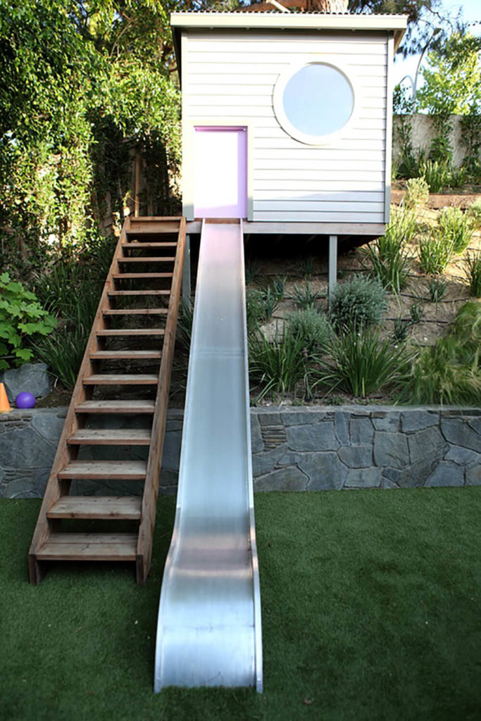 A Long Set Of Stairs Leads Up To A Playhouse Up On A Hill. A