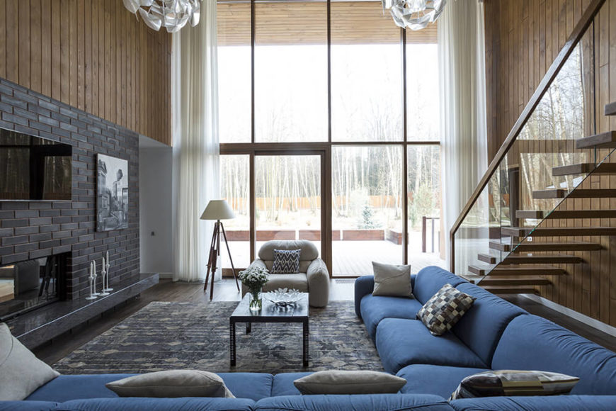 As we move into the living room, we are greeted by floor-to-ceiling panoramic windows and a door leading out to the terrace facing the birch forest. An enclosed fireplace is lined by dark charcoal gray bricks and a raised granite hearth. An enormous dusky blue sectional dominates the space, with a glass staircase leading up to the second floor