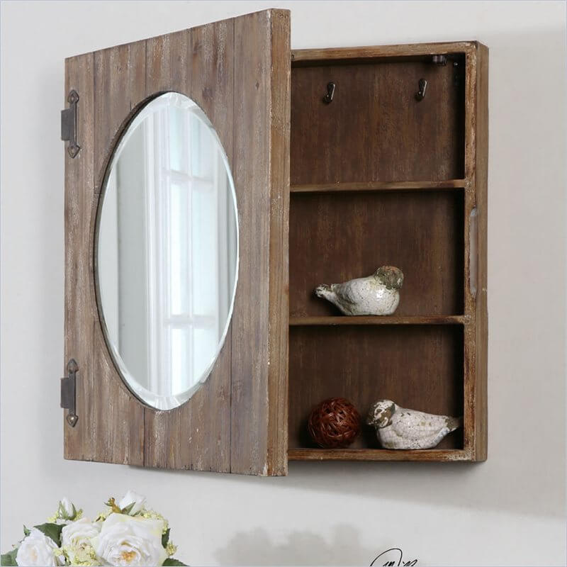 A beveled oval mirror is set into a rustic frame with iron hinges. The inside is filled with shelves and small hooks, which gives you a variety of options.