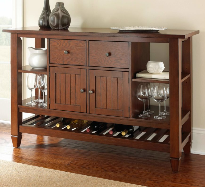The bottom of this serving table includes a large wine rack. Glasses are stored on either side of the cabinets, with drawers above.