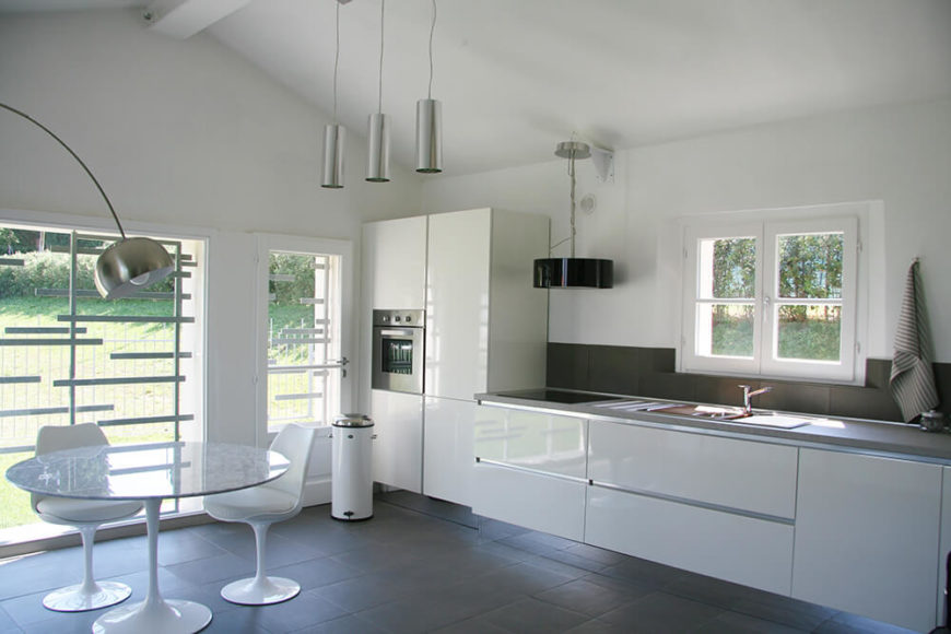 The streamlined kitchen comfortably seats two and offers up all the amenities necessary of a kitchen including a low-profile cooktop. Unique, minimal window framing adds some interest to the space without taking away from the panoramic views offered throughout the house.